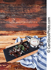 Fragrant toasts from black bread with cheese parmesan and white sauce are served on a blue napkin on an old wooden background