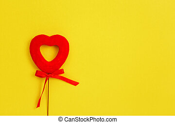 Frame and heart shaped toy on the yellow background