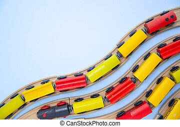 frame for text made of multicolor kids train cars bricks on wooden railway on blue background. Copyspase. top view. flat lay. Children toys on the table.