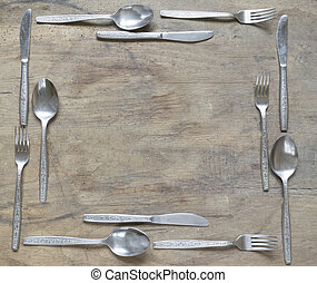 Frame from silver spoons, knives and forks on old wooden background
