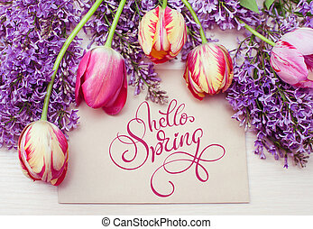 frame from tulips and lilac and place for text greeting card and text Hello Spring. Calligraphy lettering