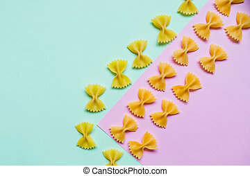 Frame from wheat pasta on pastel pink green background. Random pattern. Flat lay. Italian food concept. Bow tie Italian raw pasta fartalle pattern. Copy space. Diet and food concept.