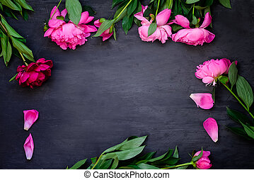 Frame made of beautiful pink peonies on wooden black background. Flat lay, top view. Floral frame. Frame of flowers. Dark Background with copy space for greeting message.