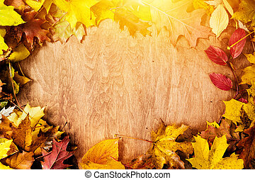 Frame made of fall leaves on wood. Autumn background