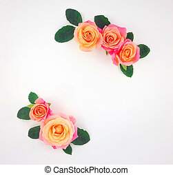 Frame made of pink-orange roses and green leaves on white background. Flat lay, top view