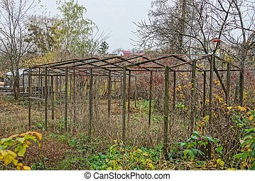 frame of an old empty greenhouse in an overgrown garden