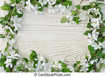 Frame of apple flowers on a white wooden background. Top view, space for text