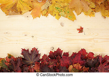 Frame of autumn leaves on a wooden background, flat lay, copy space.