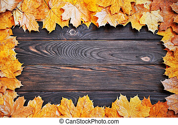 frame of autumn leaves on a wooden surface. autumn background