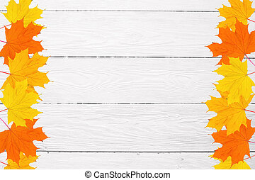 frame of autumn maple leaves on a white wooden background and space for text
