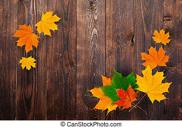 frame of autumn maple leaves on a wooden background. Design and space for text