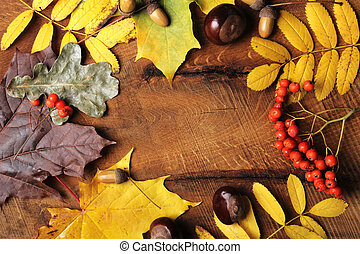 Frame of Autumn maple leaves on aged wood with copy space. Mockup for seasonal offers and holiday post card, top view