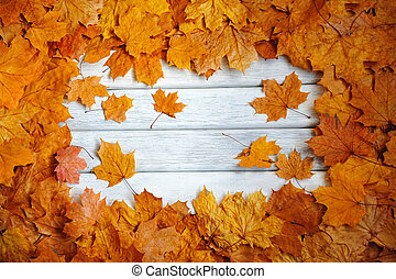Frame of autumn, yellow leaves on a white, wooden surface.