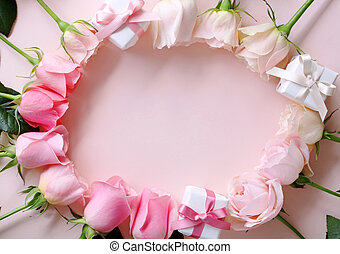 Frame of beautiful pink tone rose flowers and gift boxes on pastel pink background, top view