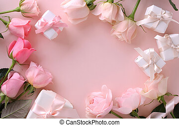 Frame of beautiful pink tone roses and gift boxes on pastel pink background, top view