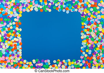 Frame of colorful confetti on blue background.
