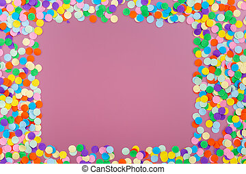 Frame of colorful confetti on pink background.