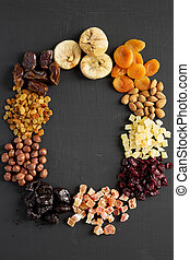 Frame of dried fruits and nuts on black surface, top view.