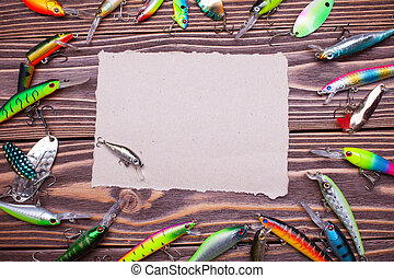 frame of fishing lures on a wooden background