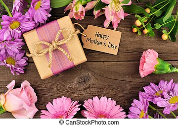 Frame of flowers with Mothers Day gift and tag against rustic wood