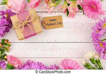 Frame of flowers with Mothers Day gift and tag against white wood