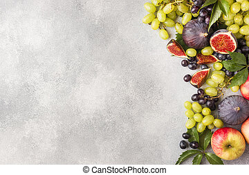 Frame of fresh autumn fruits. Grapes black and green, figs and leaves on a grey table with copy space.