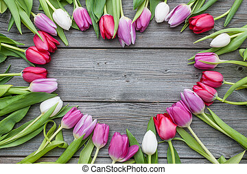 Frame of fresh tulips arranged on old wooden background -...
