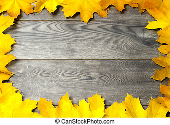 Frame of golden maple leaves on a wooden background