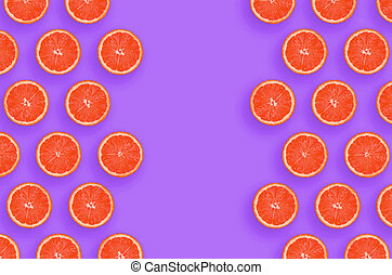 Frame of grapefruit citrus slices on bright purple background