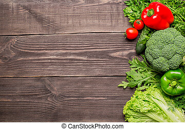 Frame of green and red fresh vegetables on wooden background, top view