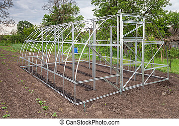 Frame of greenhouse is installed in garden