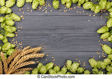 Frame of hop cones with ears of wheat on black wooden background. Top view with copy space for your text