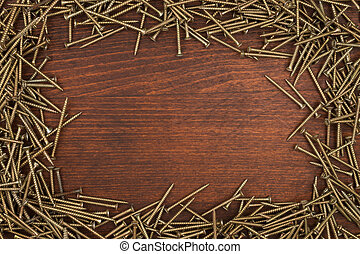 Frame of new black screws lying on a wooden surface.