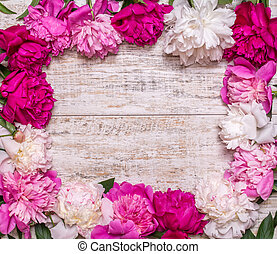 Frame of peonies on a wooden background. Floral design. Pink and purple spring flowers