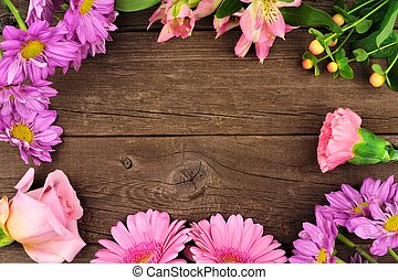 Frame of pink and purple flowers against a rustic wood background