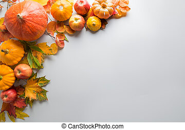 Frame of pumpkin and maple leaves on wooden board with space for text. Fall pattern. Top view.