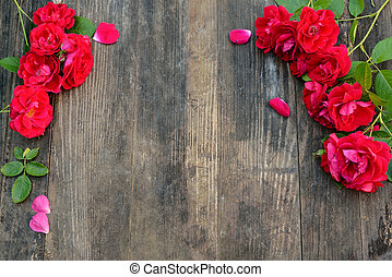 Frame of red roses on a wooden background with space for text.