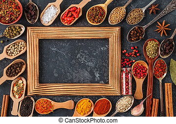 Frame of various spices on dark stone table