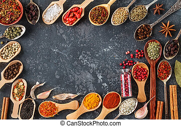 Frame of various spices on dark stone table.