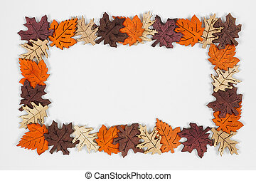 Frame of wooden autumn leaves over a white background