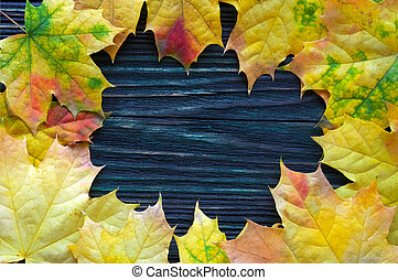 Frame of yellow, autumn, maple leaves on a wooden background. Top view. Template for advertising, seasonal sale.