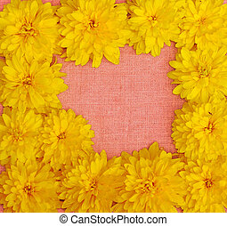Frame of yellow flowers against a background of pink cloth