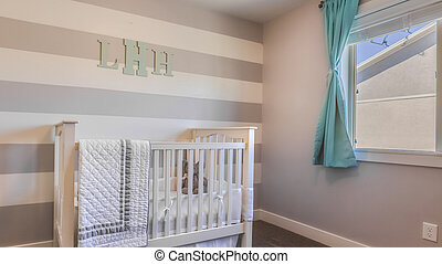 frame Panorama Interior of a nursery with white crib and monogram letters on the striped wall