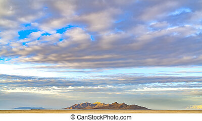 frame Panorama Panorama of a sandy lake shore under a blue sky filled with puffy clouds