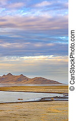 frame Vertical Panorama of a calm lake with vast sandy shore under cloud filled sky