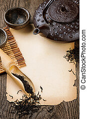 Frame with Asian teapot, dried black tea and vintage paper