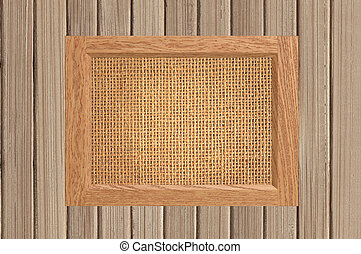 frame with empty canvas linen on wooden background