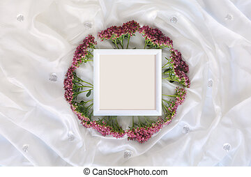 Frame with flowers on white silk