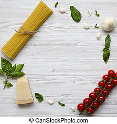Frame with ingredients for cooking pasta on a white wooden background, top view. Flat lay. From above, overhead.