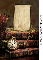 Vintage wood desk with Antique Frame with old photo paper texture, Books and Old Pocket Clock in Low-key.